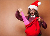 A guy dressed in the style of a hipster look Christmas gifts out — Stock Photo