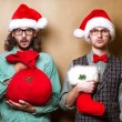Two hipster in Santa Claus clothes with the bag of the presents — Foto de Stock