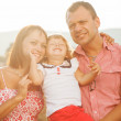Happy mother, father and daughter in sunset — Stock Photo #34921771