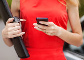 Young beautiful woman writes an SMS to your mobile phone. — Stock Photo