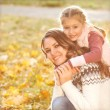 Young mother and her toddler girl have fun in autumn — Stock Photo