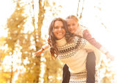 Mother giving daughter piggyback ride in autumn woodland — Stock Photo