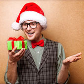 Smiling funny child in Santa red hat holding Christmas gift — Stock Photo