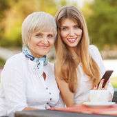 Adult mother and daughter drinking tea or coffee — Stock Photo