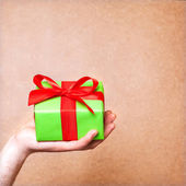 Hands holding small gift with ribbon. — Stock Photo