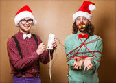 Two guys to play with Christmas garland — Zdjęcie stockowe