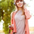 Young beautiful girl listening to MP3 player on the street — Stock Photo
