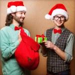 Hipster Santa Claus giving a gift — Stock Photo #37019037