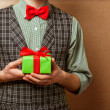 Guy holding a gift in a suit and bow tie — Stockfoto