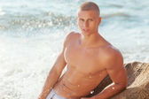 Portrait of a handsome young muscular man in swimtrunks — Stock Photo