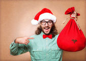 Hipster in Santa Claus clothes with the bag of the presents — Stock Photo