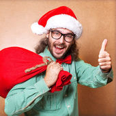 Hipster Santa Claus with the bag of the presents shows cool — Stock Photo