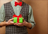 Guy holding a gift in a suit and bow tie — Foto Stock