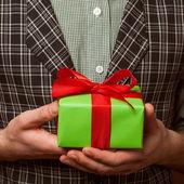 Killen som innehar en gåva i en kostym och slips typ fluga i en bur — Stockfoto