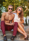 Young couple kissing with sunglasses outdoors — Stock Photo