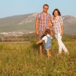 Father mother and daughter walking on the field — Stock Photo