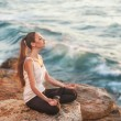 Girl in lotus pose at sunset — Stock Photo #37374523