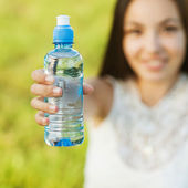 Portrait half face of young woman holding water bottle at summer — 图库照片
