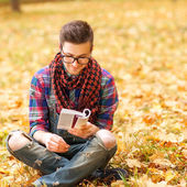 Young hipster relaxed man reading book in nature, back on tree, — Stock Photo