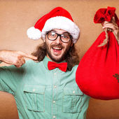 Guy holding a gift and emotionally happy Christmas — Stok fotoğraf