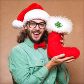 Guy holding a gift and emotionally happy Christmas — Stock Photo