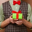 Guy holding a gift in a suit and bow tie — Stock Photo