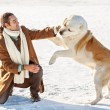 Man and central Asian shepherd playing with his dog outdoors — Stock Photo #37731215