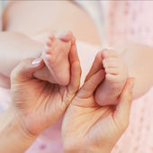 Baby-Füße, die Haende in Mütter-Hände. — Stockfoto