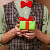 Guy holding a gift in a suit and bow tie — Foto de Stock