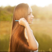 Beautiful girl combs her hair — Stock Photo