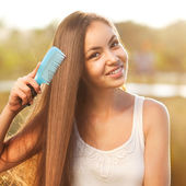 Beautiful girl combs her hair Asian appearance — Stock Photo