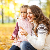 Mother and daughter having fun in the autumn park — Fotografia Stock
