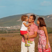 Šťastná matka, otec a dcera v západu slunce — Stock fotografie