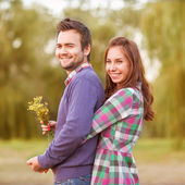 Young couple in love walking in the autumn park near the river. — Foto de Stock