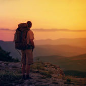 Guy in the mountains at sunset. the concept of freedom — Stock Photo