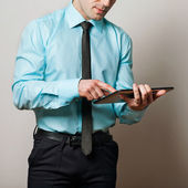 Serious young male executive using digital tablet — Stock Photo