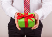 Businessman holds out the gift box ,isolated background — Stock Photo
