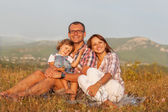 Happy mother, father and daughter in sunset — Stock Photo
