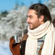 Young man with tea standing in snowy woods — Stock Photo #39411693