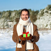 Man with gift waiting his woman in the woods in winter — Stock Photo