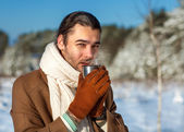 Young attractive man drinking tea outside in winter time — Stock Photo