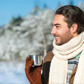 Young man with tea standing in snowy woods — ストック写真