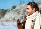 Young man with tea standing in snowy woods — Stock Photo