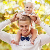 Happy young man holding a smiling 7-9 months old baby — ストック写真