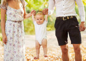 Happy young family holding a smiling 7-9 months old baby — Stock Photo