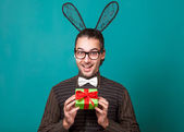 Fashion guy in bunny ears of holding gift. valentine's day — Stock Photo