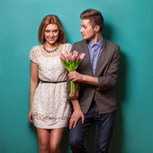 Beautiful couple in love with flowers tulips — Stock Photo