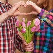 Young couple in love make a heart and hands are holding a bouquet of tulips — 图库照片