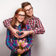 Young couple in love make a heart and hands are holding a bouquet of tulips — Stock Photo #39870317