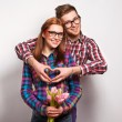 Foto de Stock  : Young couple in love make a heart and hands are holding a bouquet of tulips